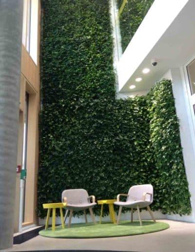 Großflächige Gestaltung durch eine grüne Wand über mehrere Etagen